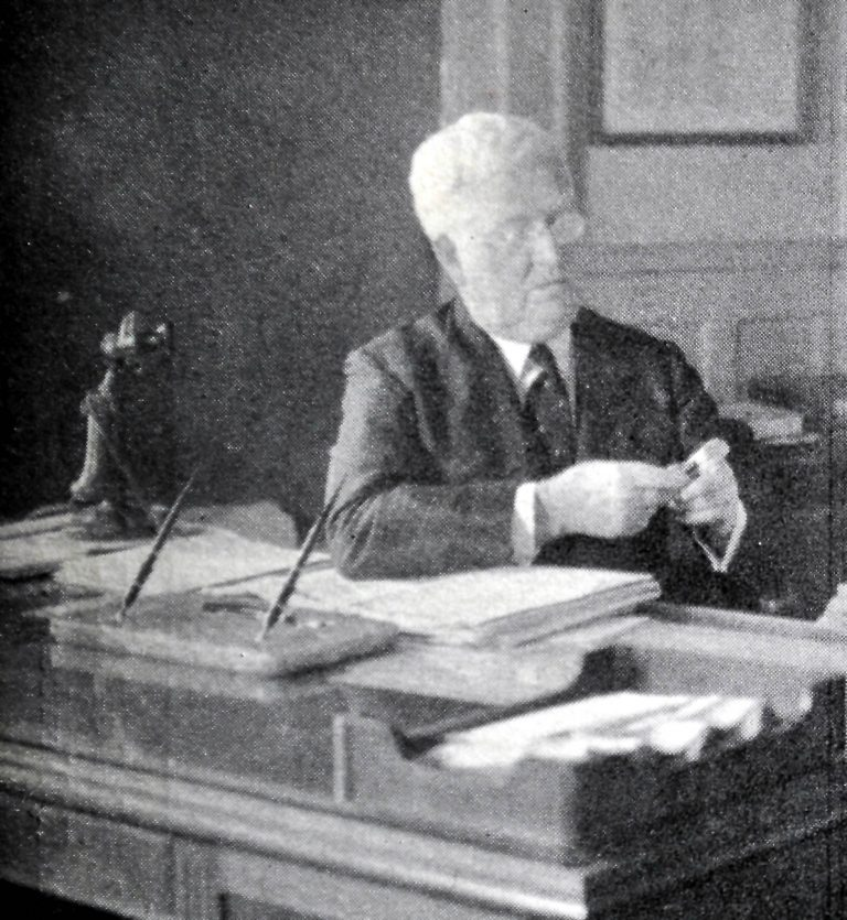 W.A. Sheaffer inspects pen in his office.